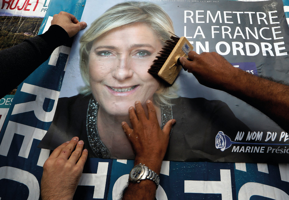 Members of the French National Front (FN) political party paste a poster on a free billboard for French National Front (FN) political party leader Marine Le Pen as part of the 2017 French presidential election campaign in Antibes, France, April 14, 2017.   REUTERS/Eric Gaillard  TPX IMAGES OF THE DAY - RTX35JCI