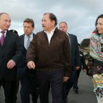 CORRECTS DAY AND DATE - In this photo released by the Nicaraguan Presidential Press Office, Nicaragua's President Daniel Ortega, center, and first lady Rosario Murillo walk with Russian President Vladimir Putin, left, upon his arrival at the Augusto C. Sandino International Airport, in Managua, Nicaragua, Friday, July 11, 2014. Putin is continuing a Latin American tour, that includes Argentina and Brazil, aimed at building Russia's influence and investments in the region. (AP Photo/Nicaragua Presidential Press Office, Cesar Perez)