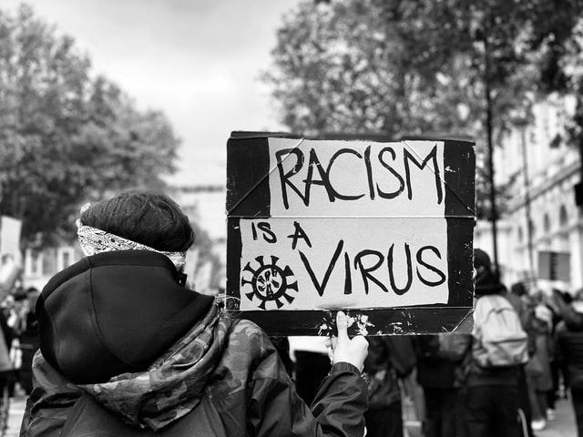 Cartaz diz: racismo é um vírus